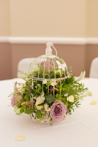 Second-hand birdcages filled with flowers became perfect table centres.